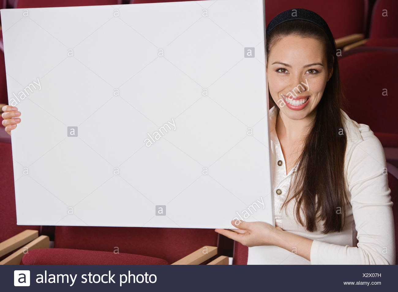 Woman sitting in auditorium, holding empty placard - Stock Image