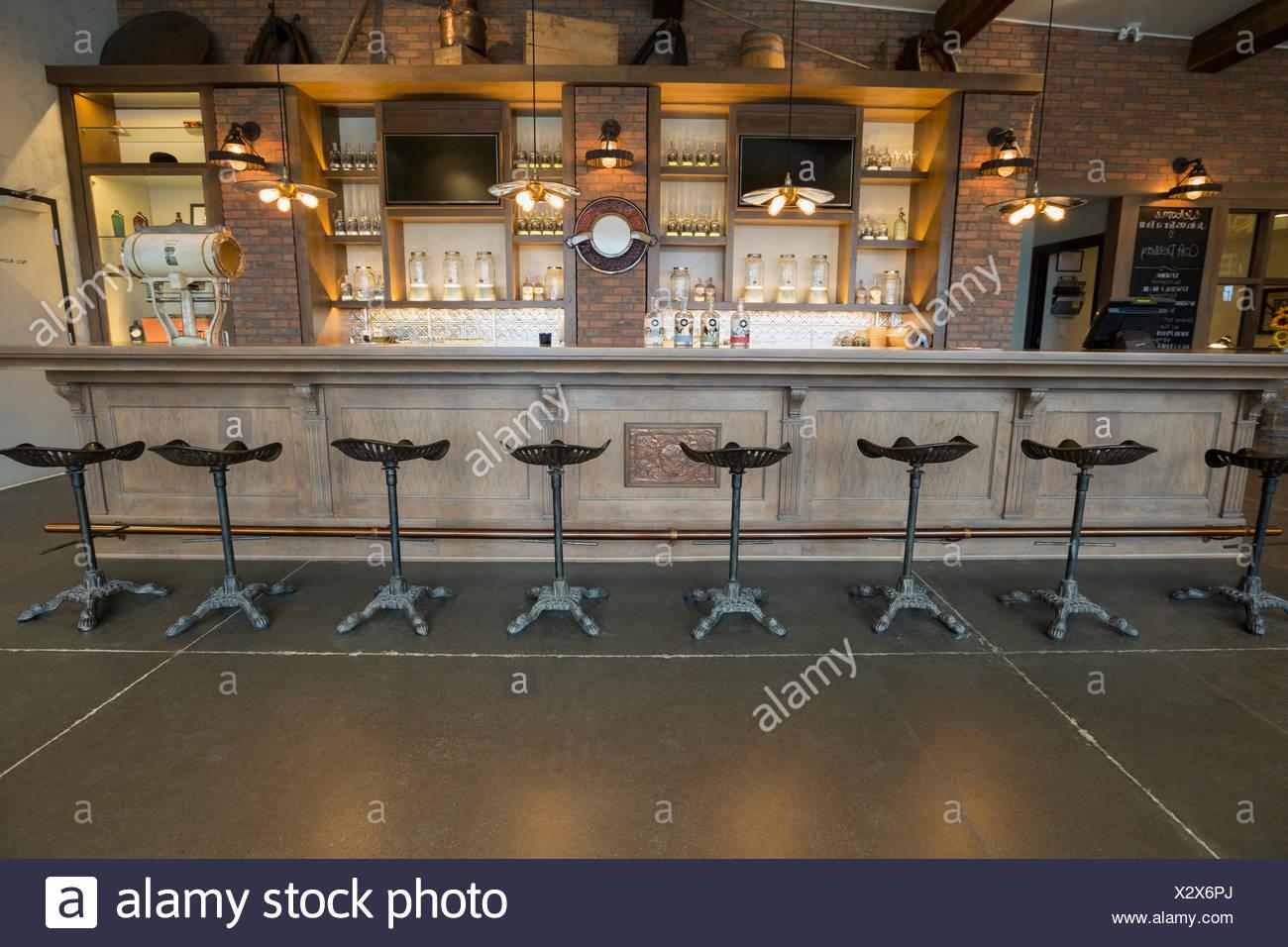 Stools lined along empty distillery bar - Stock Image