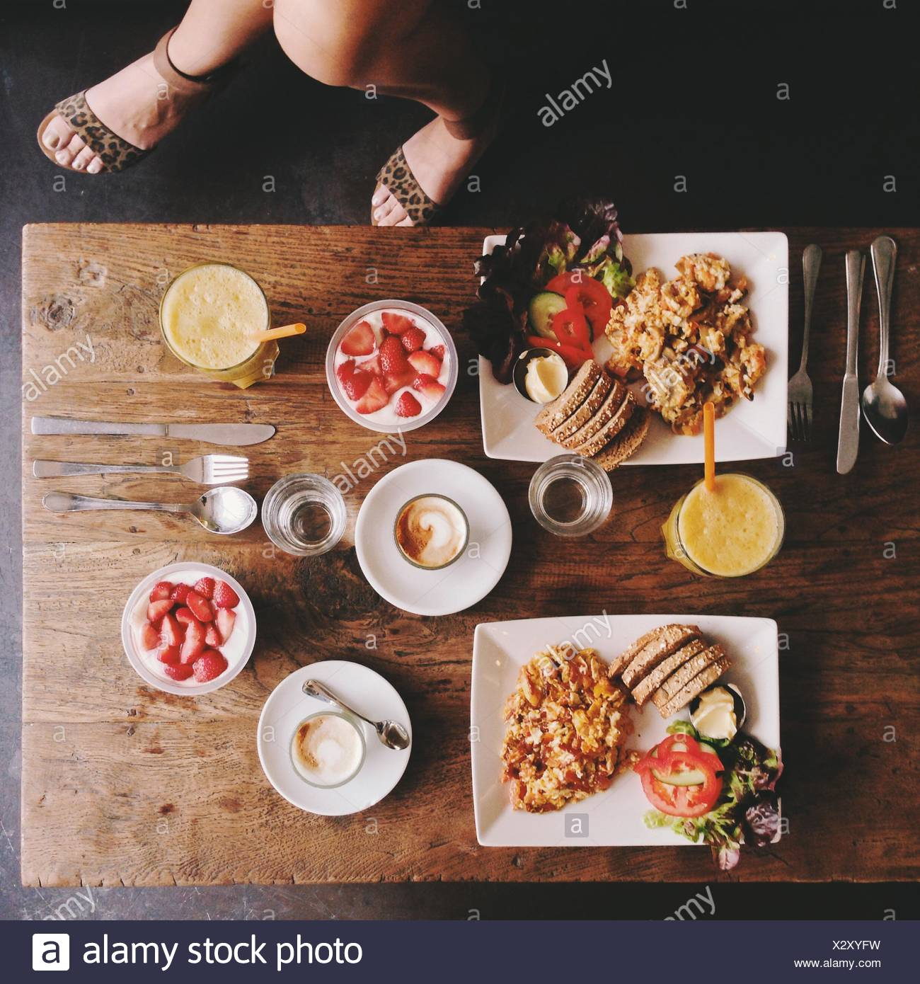Overhead view of woman's legs and breakfast table - Stock Image