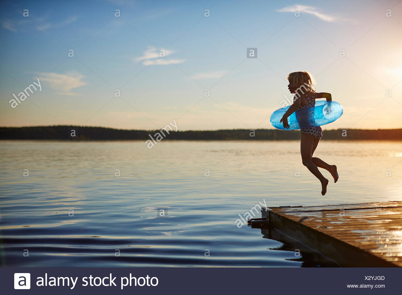 Girl jumping off a pier - Stock Image