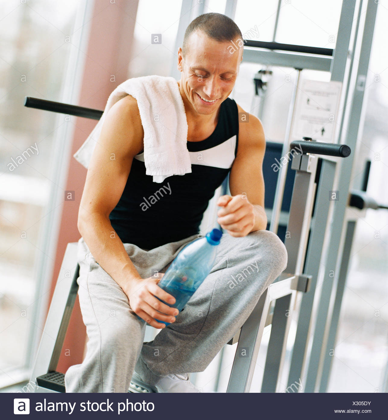 30-34 years 45-49 years activity adults only athlete bodybuilding bottle bottle of water color image exercising gym happy - Stock Image