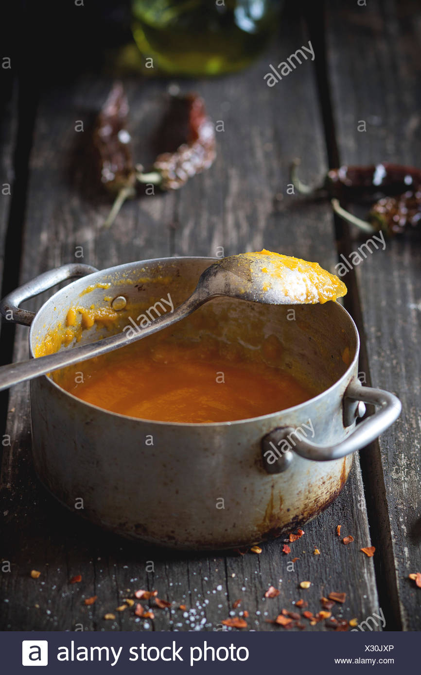 Aluminum pan with remains of carrot cream soup with red hot chili pepper. Over old wooden table with vintage spoon and dry peppe - Stock Image