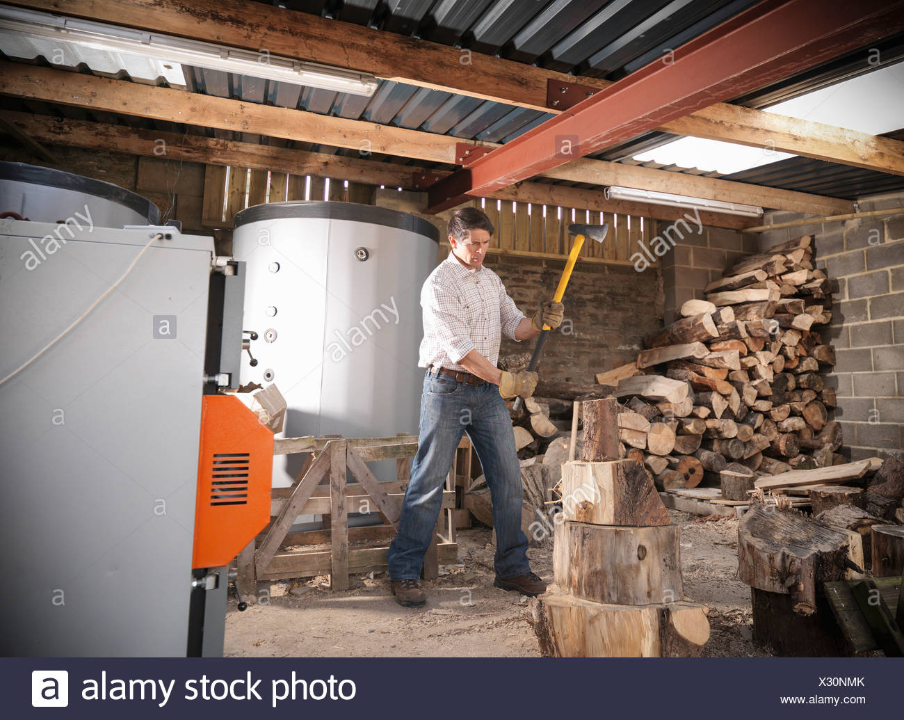 Man chopping wood in shed - Stock Image