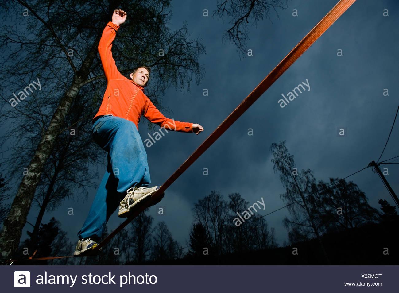 A man balancing on a cord. - Stock Image