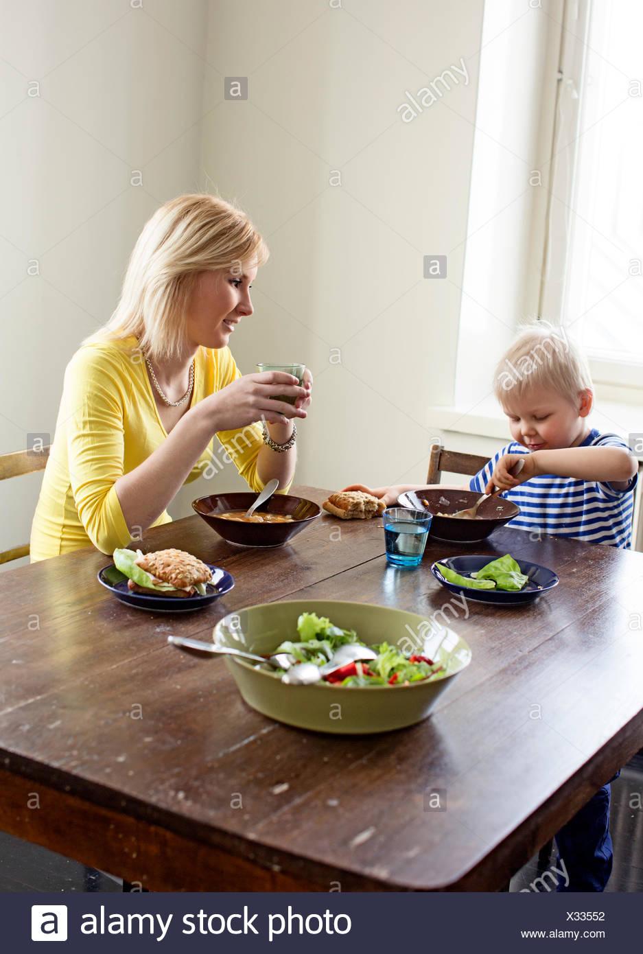 Finland, Helsinki, Kallio, Mother and son having lunch - Stock Image