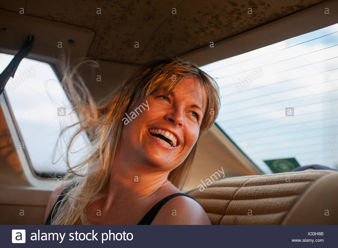 Blonde woman laughing on back seat of car - Stock Image