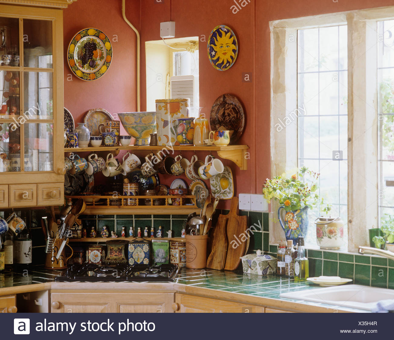 Colorful Pottery Plates On Wall Above Bowls And Cups On Pine Shelves