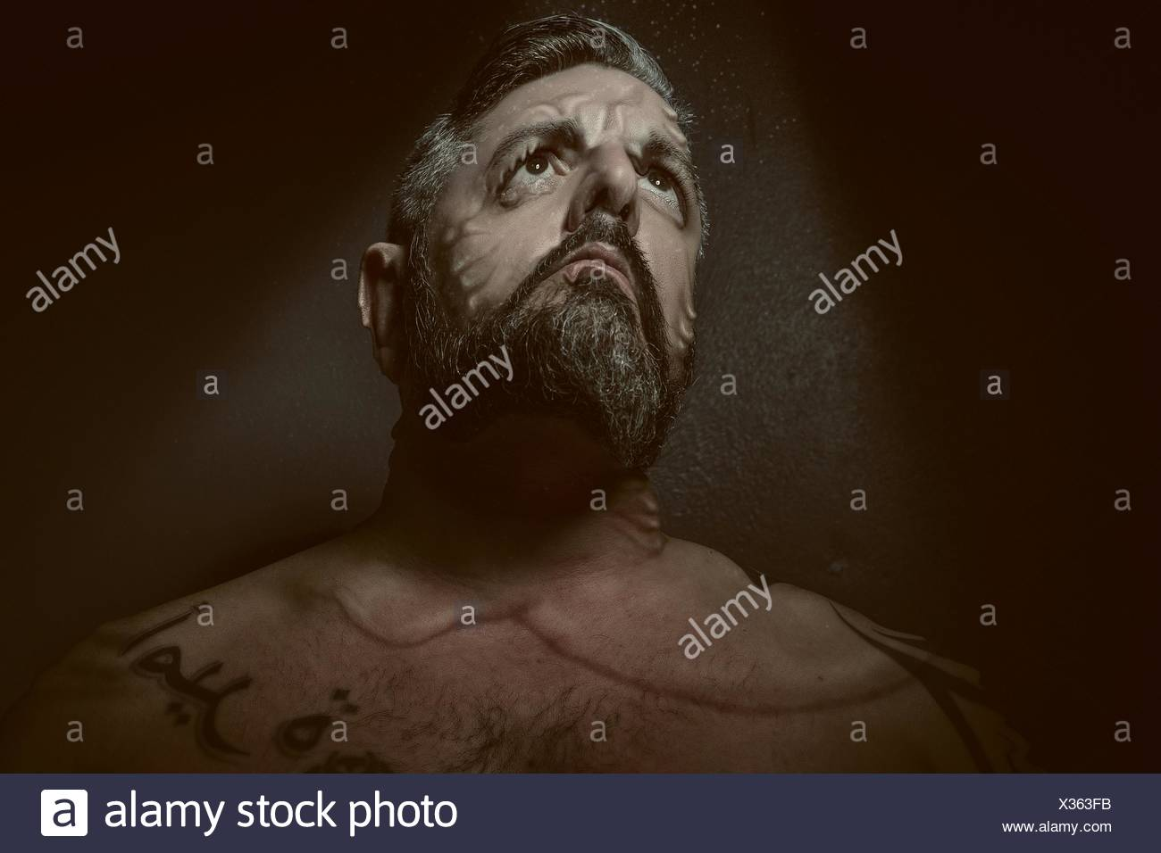 Bizarre Shot Of Man With Disfigured Face Looking Up - Stock Image