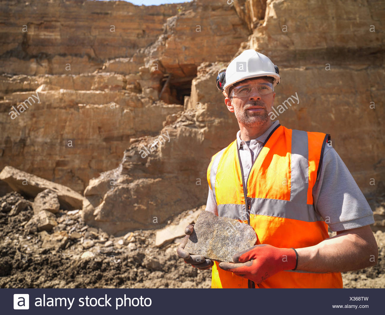 Quarry worker inspecting stone in quarry, looking away - Stock Image