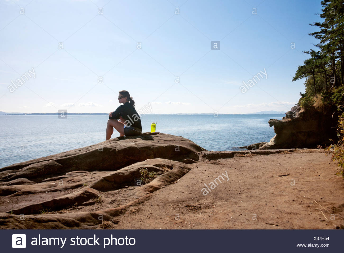 A woman sits on sandstone on the coastline of Larrabee State Park. - Stock Image