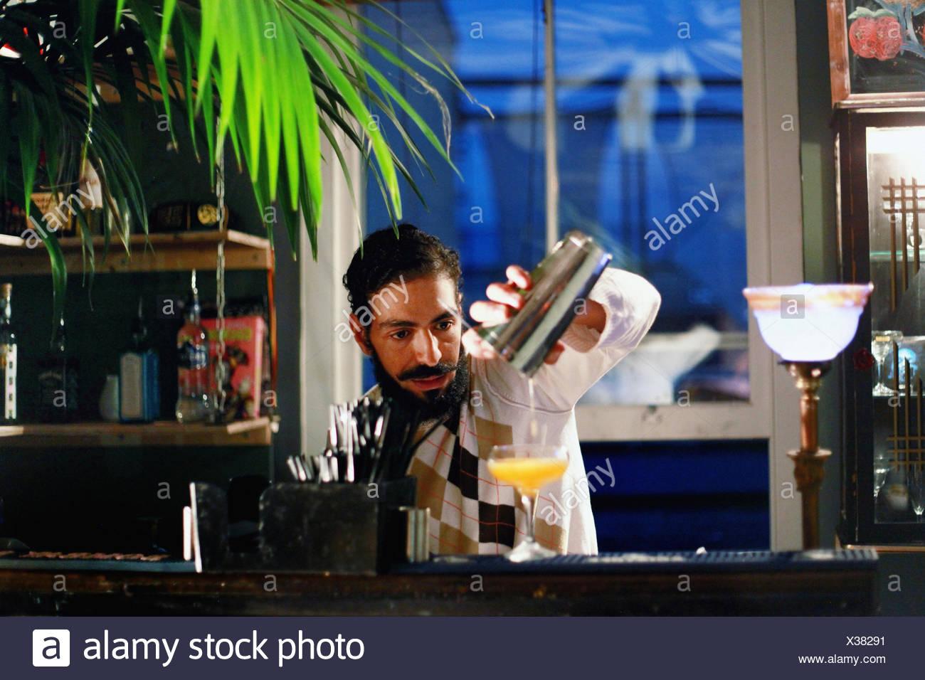Bartender serving cocktail at bar - Stock Image