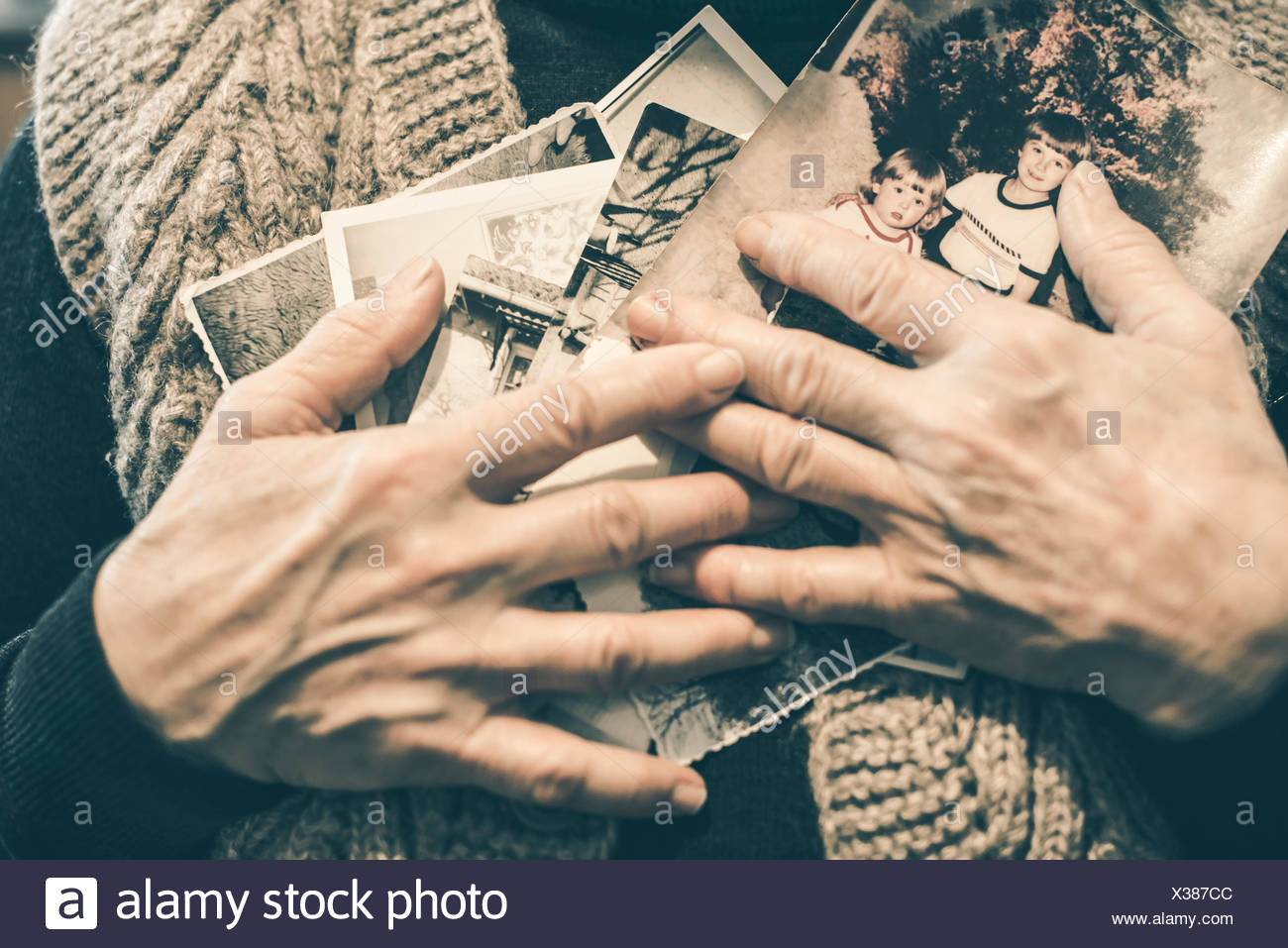 Hands of senior woman holding old photographies, close-up - Stock Image