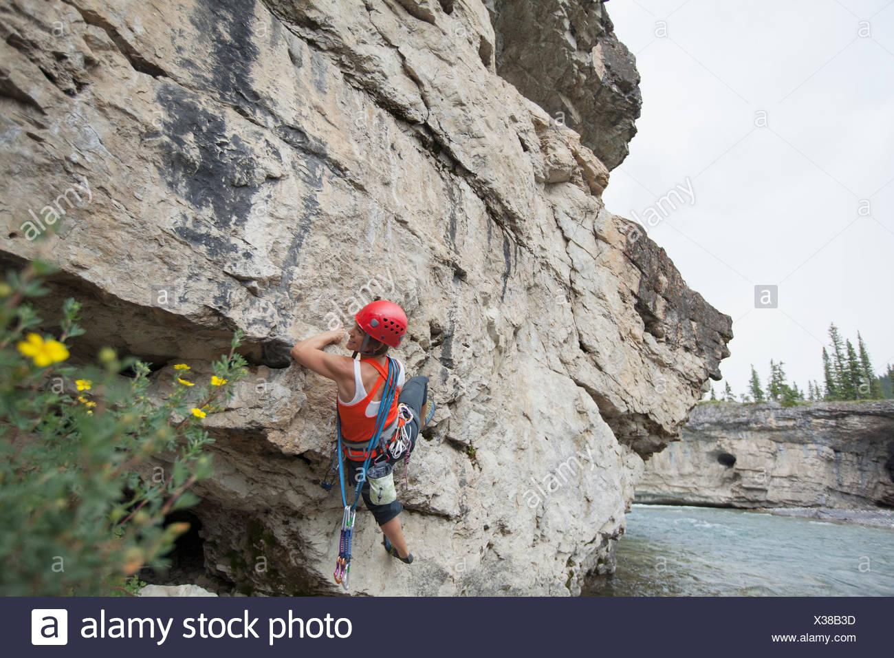 female rock climber scaling rock face - Stock Image