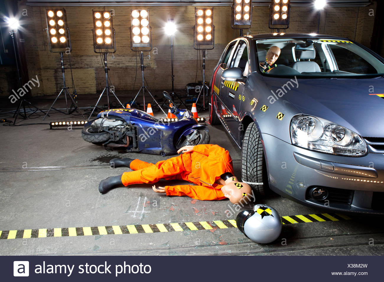 A crash test dummy on ground after scooter crashed into car - Stock Image