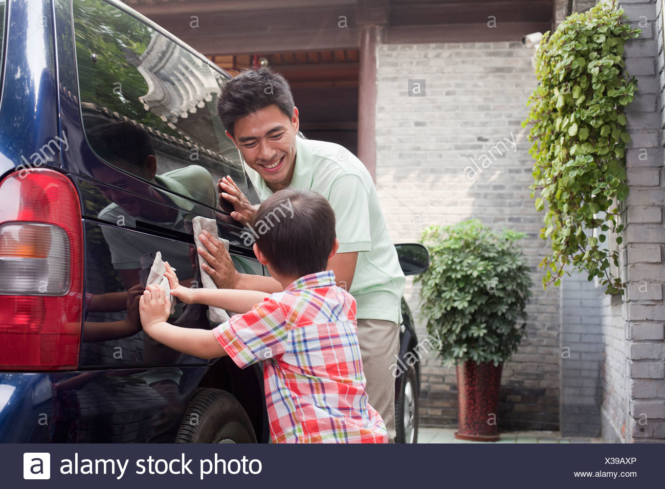 Father and Son Clean their Minivan Together - Stock Image