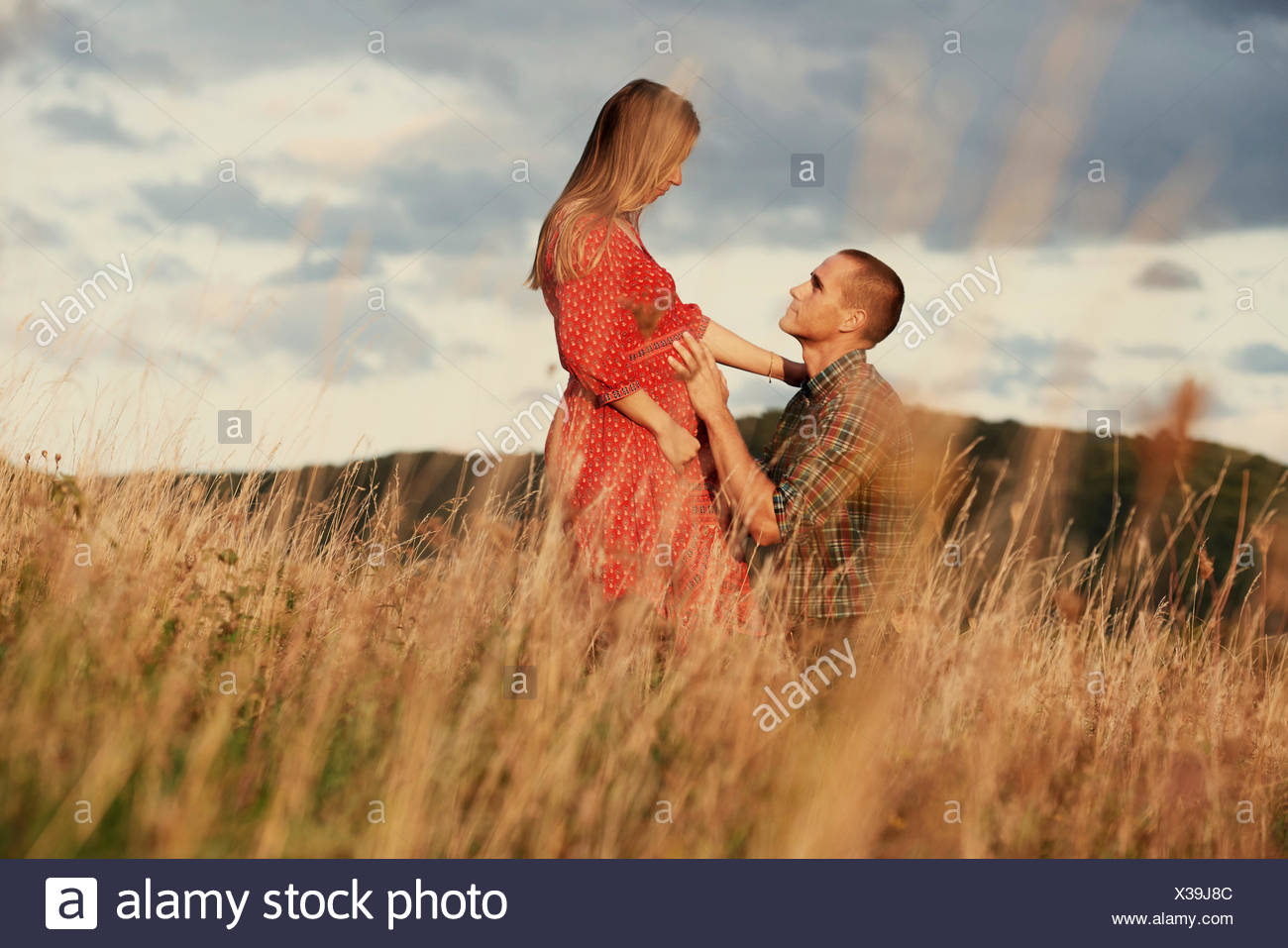 Mid adult man kneeling with hand on pregnant wife's stomach in field - Stock Image