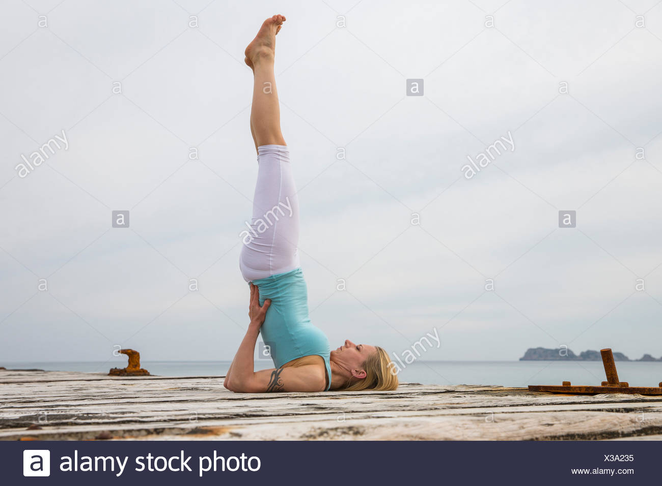 Mid adult woman with legs raised practicing yoga on wooden sea pier - Stock Image