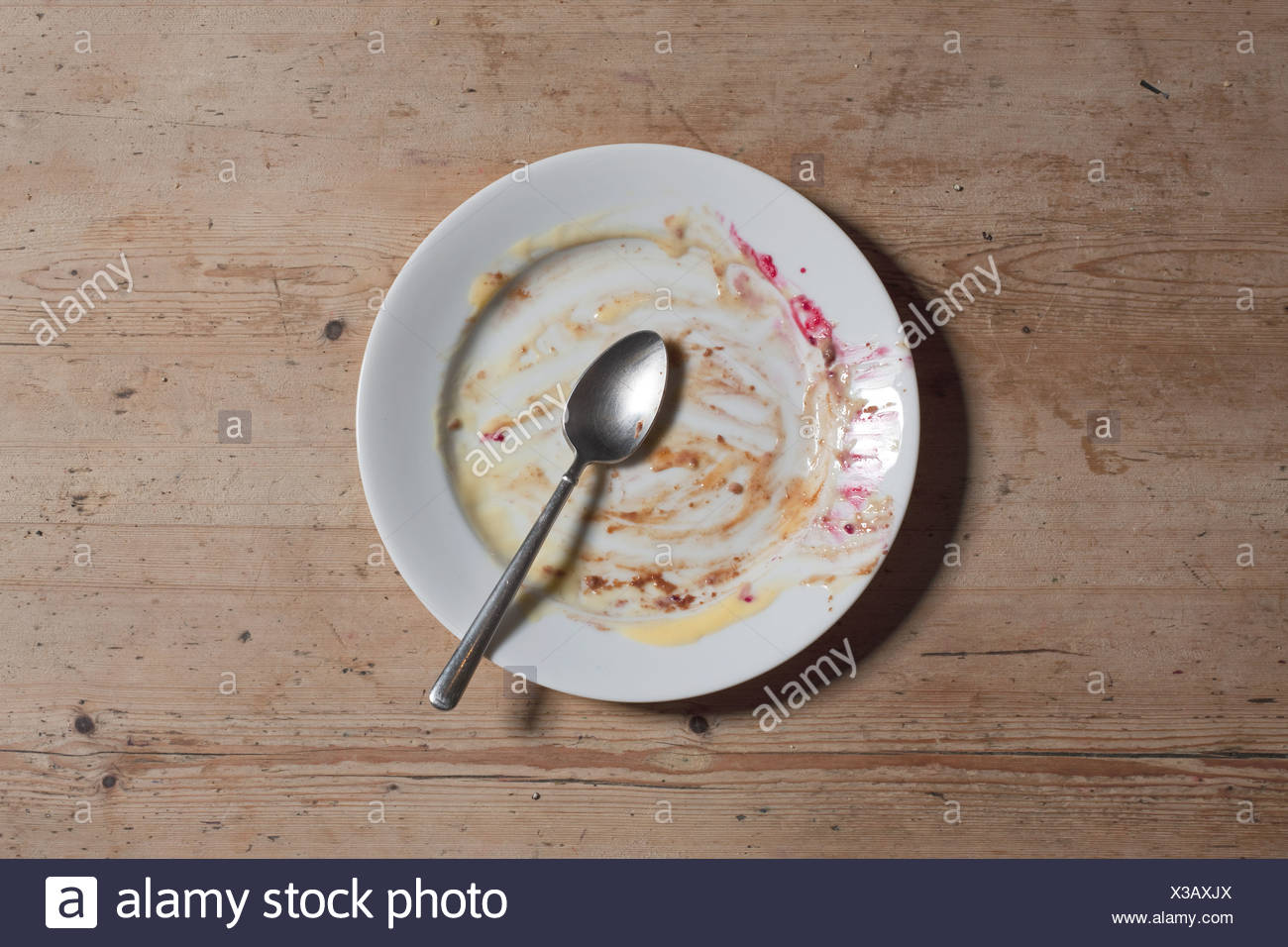 Remains of eaten pudding on plate - Stock Image