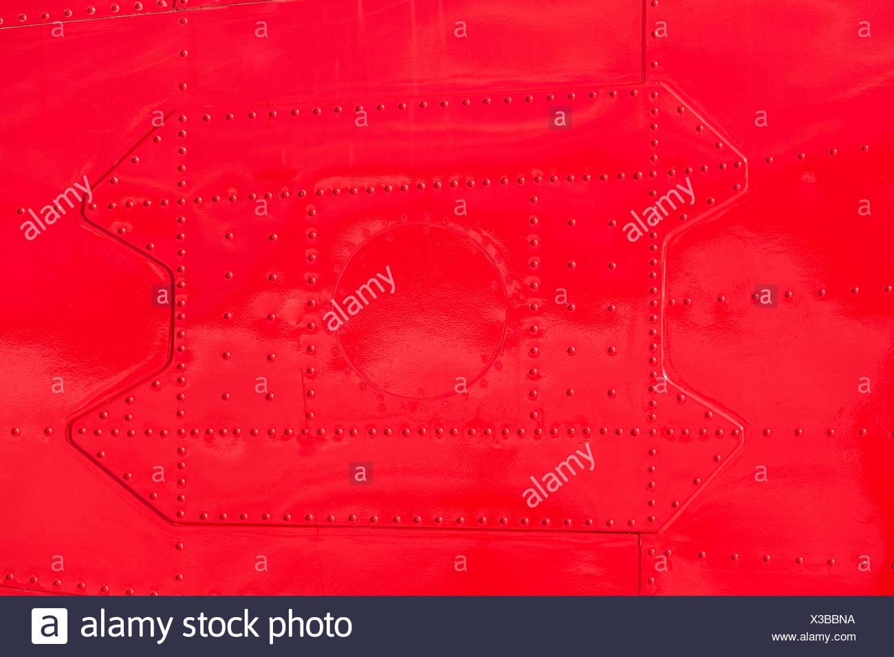 Red painted riveted metal airplane fuselage skin - Stock Image