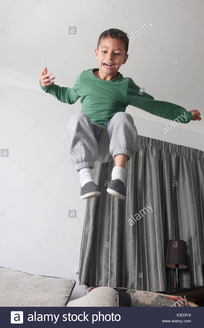 hyperactive child leaping off sofa - Stock Image