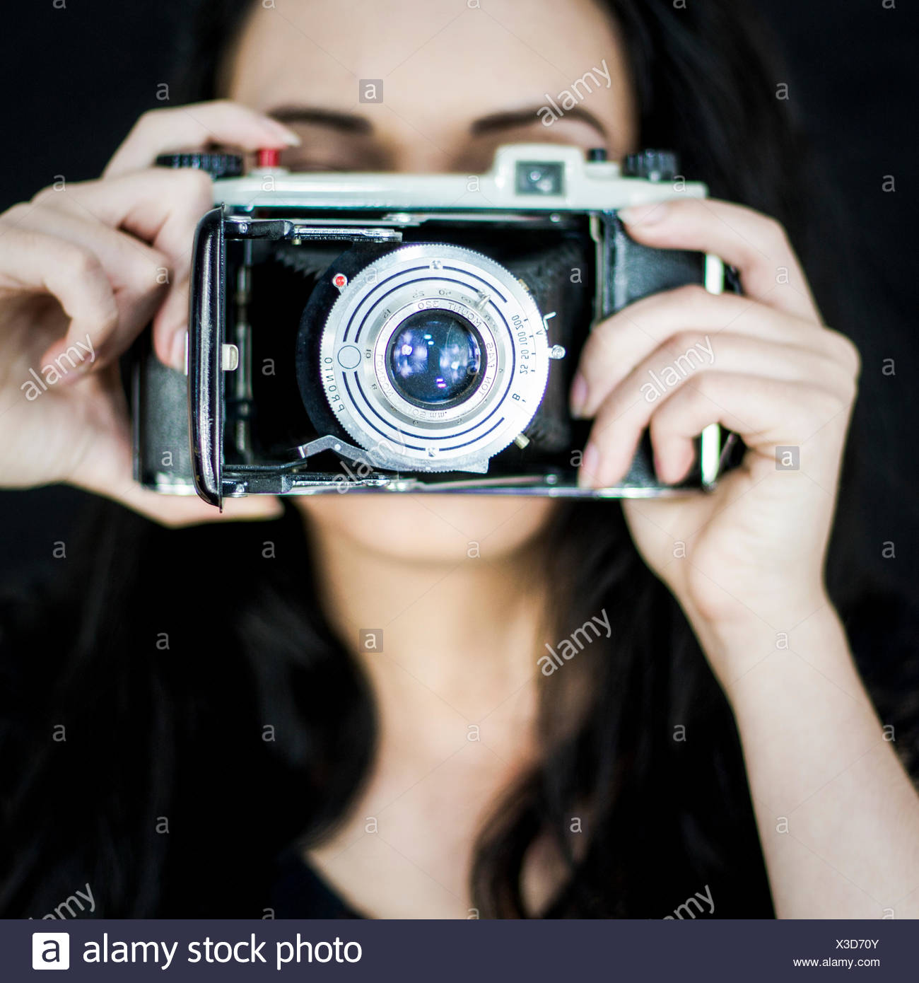 Young woman with old camera - Stock Image