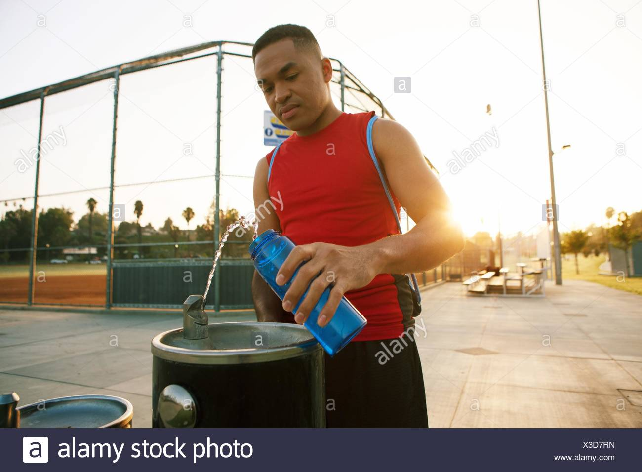 Young man filling water bottle from drinks fountain - Stock Image