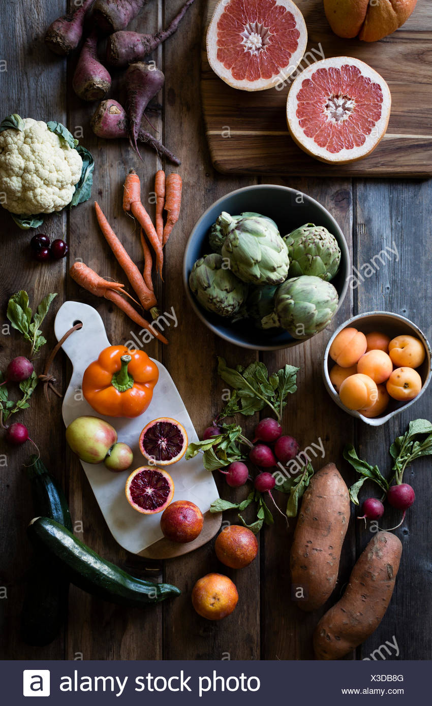 Fruit and vegetables laid out on a farm table. Carrots, cauliflowers, beets, peaches, oranges. - Stock Image