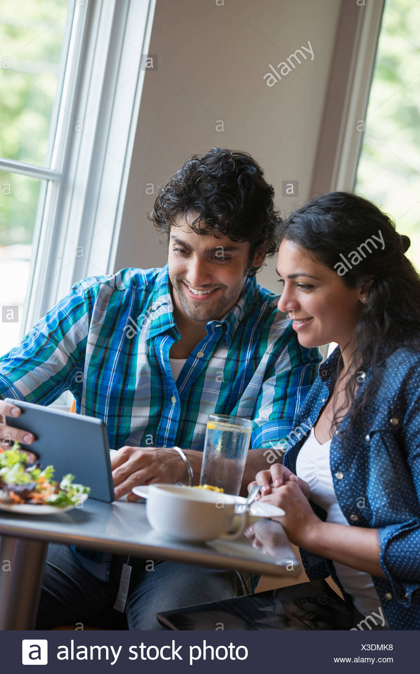 A couple seated looking at a digital tablet. - Stock Image