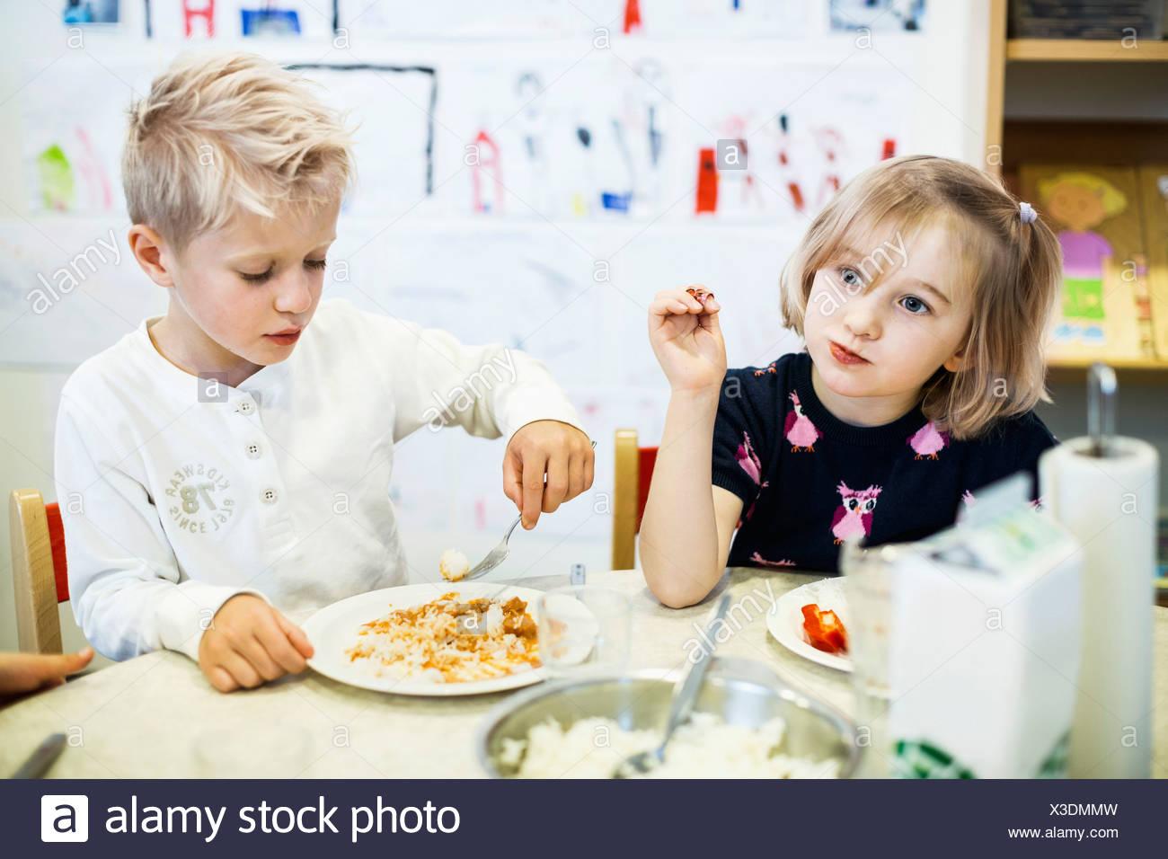 Elementary students having food in kindergarten - Stock Image