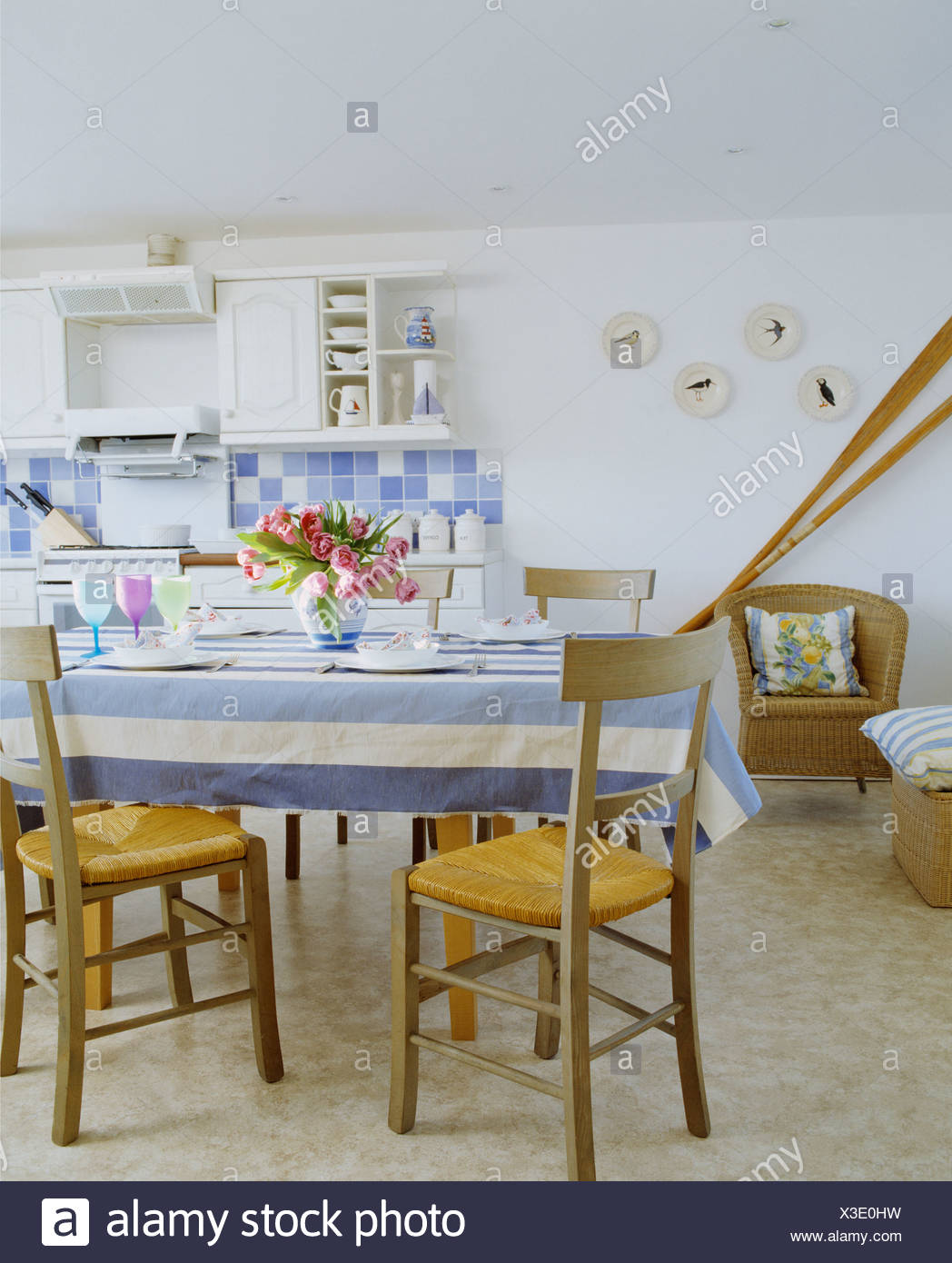 Blue+white striped cloth on table with rush-seated chairs in white on