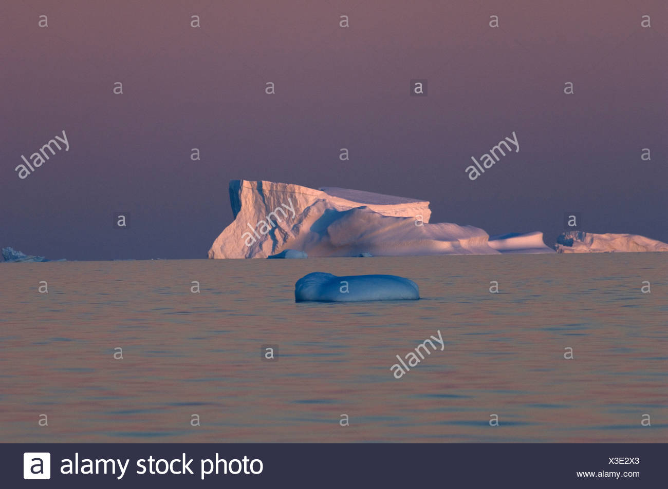 The pink sunset turns the normally blue water purple. The west coast of Antarctica's peninsula known as Graham Land. - Stock Image