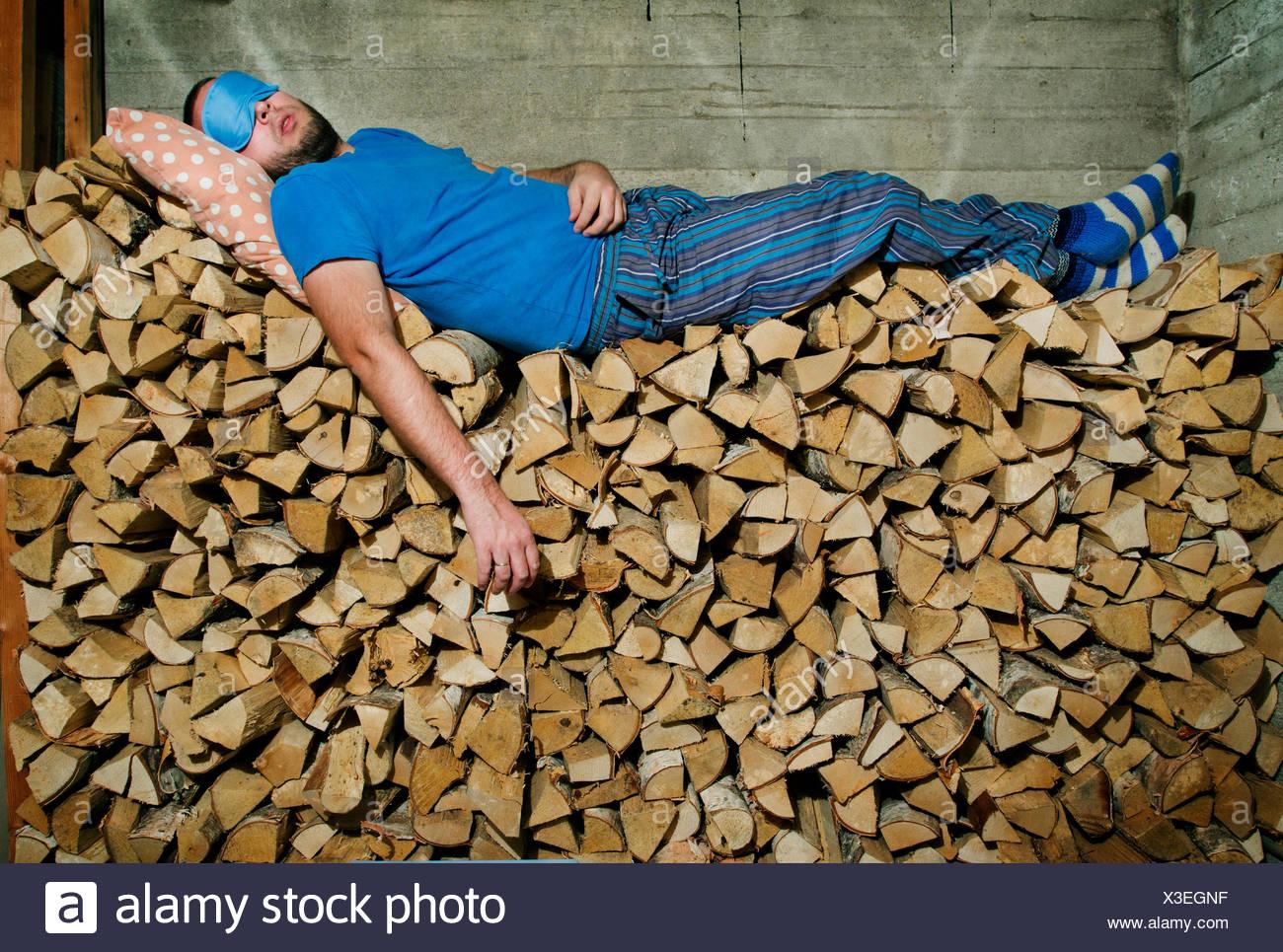 Finland, Heinola, Man sleeping on pile of firewood - Stock Image