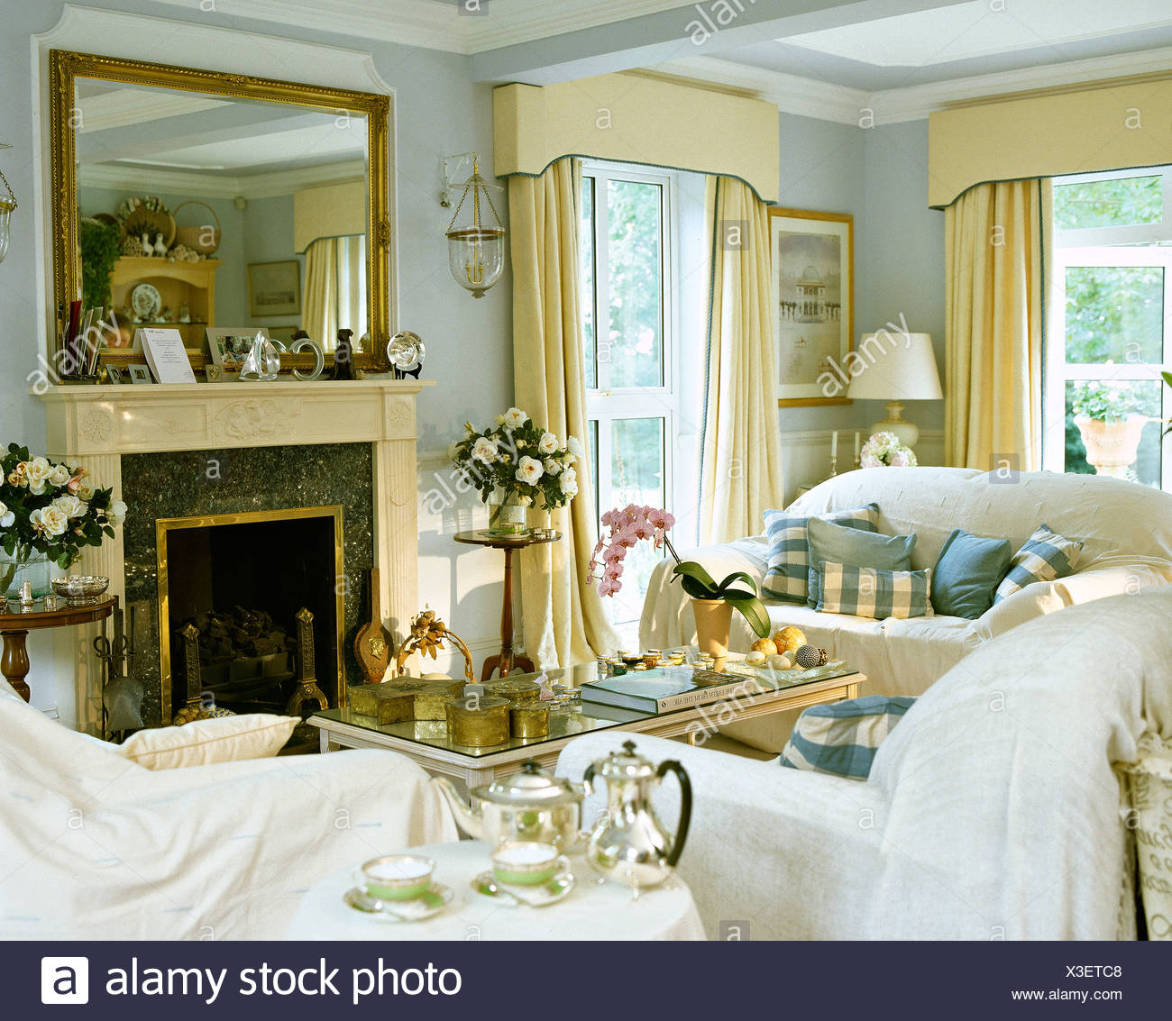 White Throws On Sofas In Pale Blue Living Room With Large Mirror Above  Fireplace And Cream Drapes On Windows
