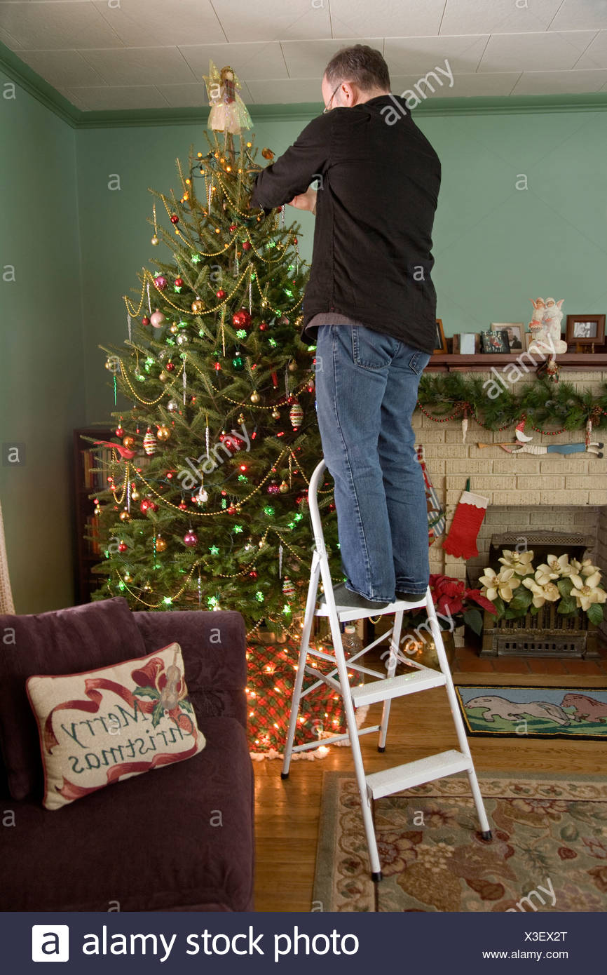 man standing on a ladder decorating the christmas tree whitby ontario