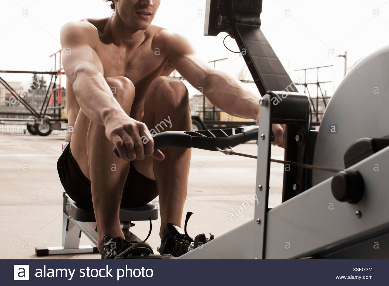 Man using exercise equipment in gym - Stock Image