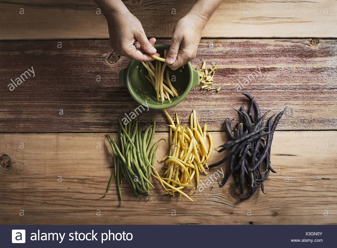 Organic green yellow and black haricot beans fresh vegetables being topped and tailed by a person before cooking and eating - Stock Image