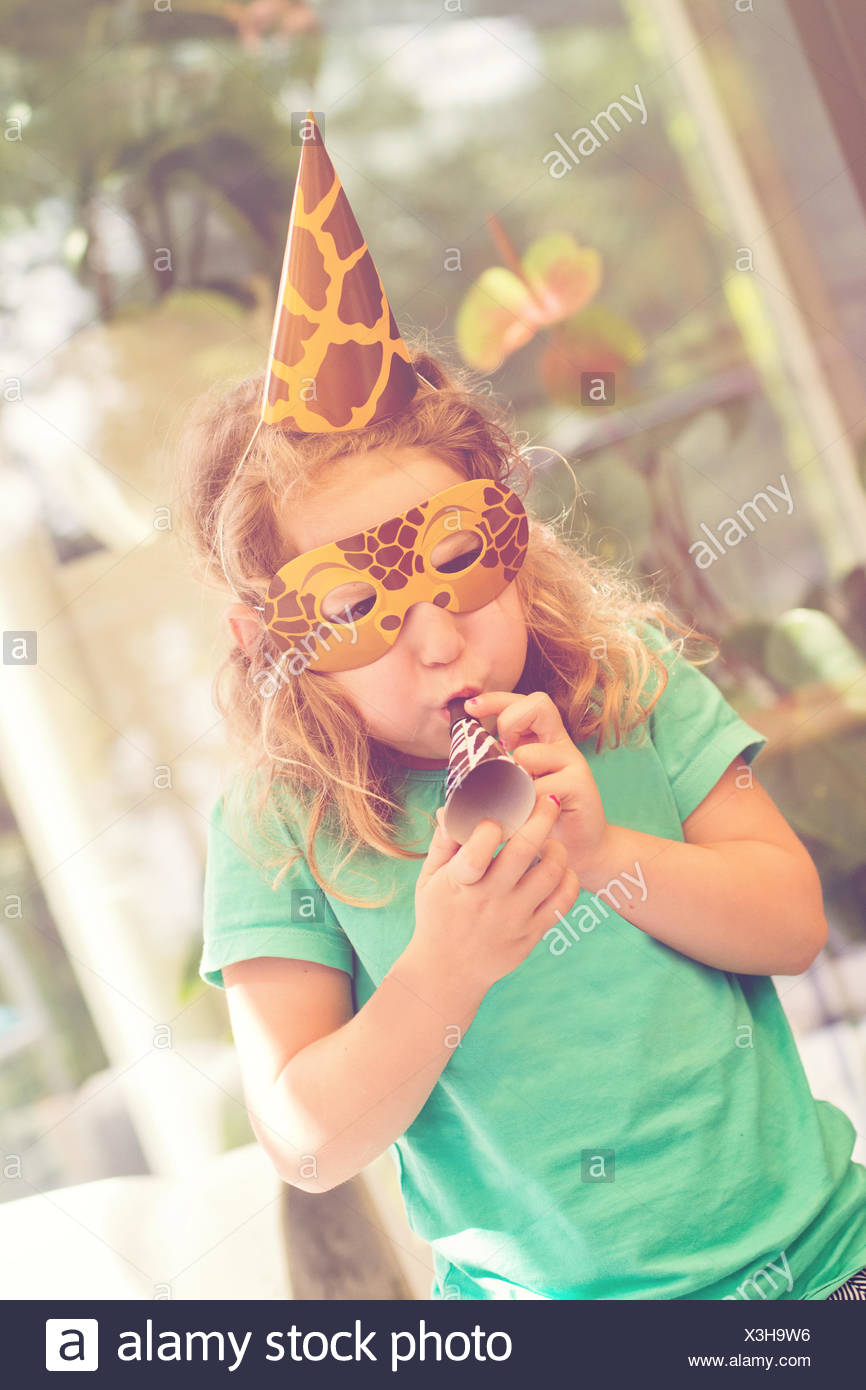 Girl in a mask at a birthday party with a party blower - Stock Image