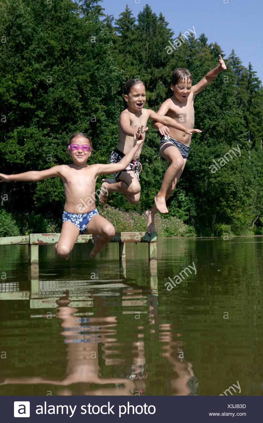 three children jumping into lake - Stock Image