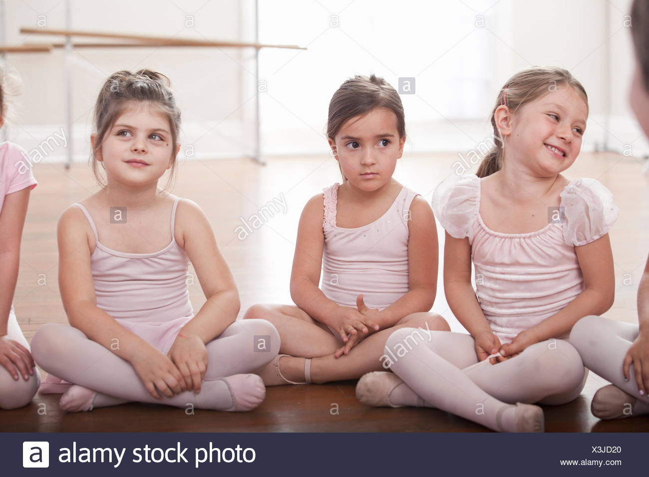 Group of girls sitting on floor in ballet school - Stock Image
