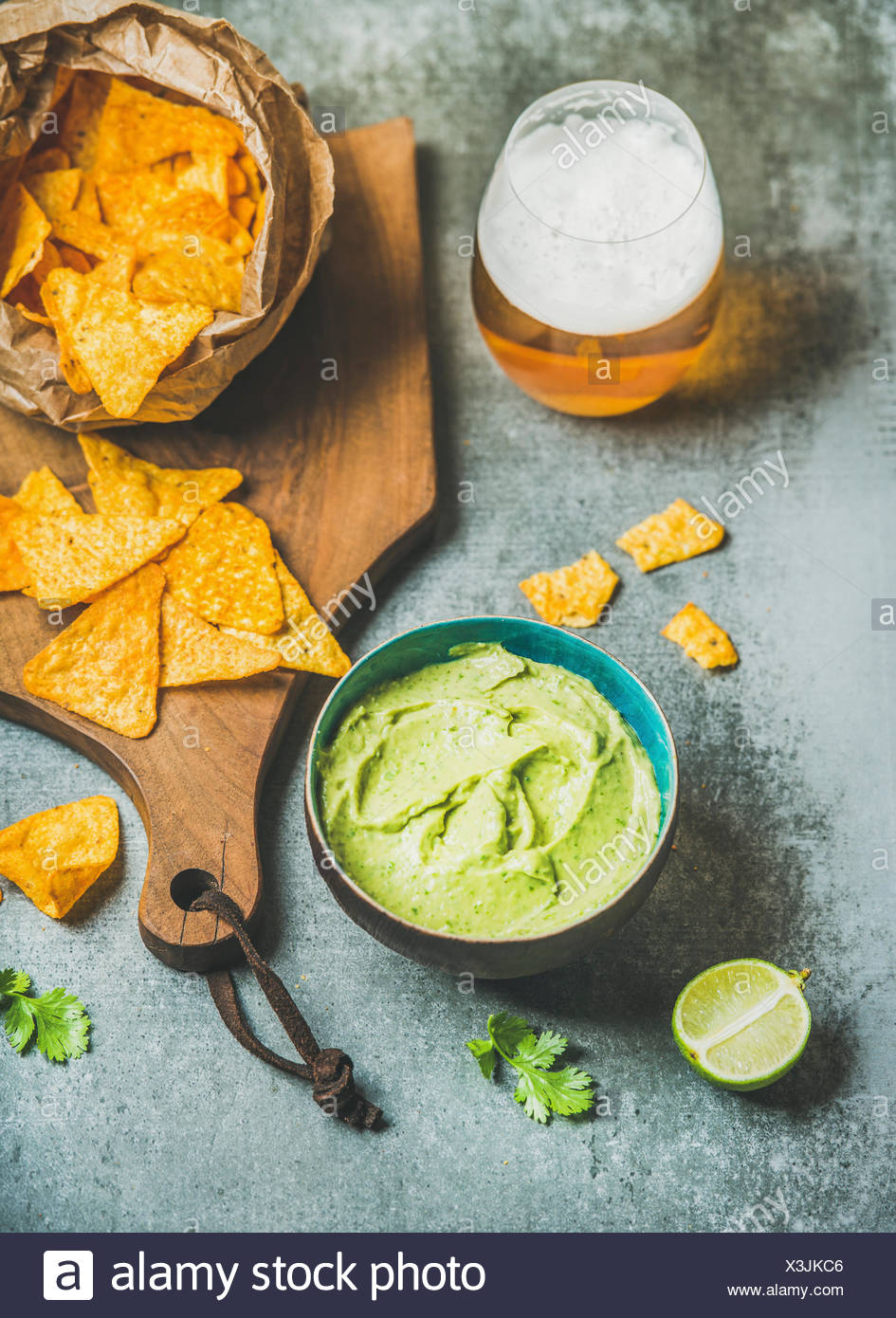 Mexican corn chips, fresh guacamole sauce and glass of beer on wooden serving board over grey concrete table background, selective focus, vertical com - Stock Image