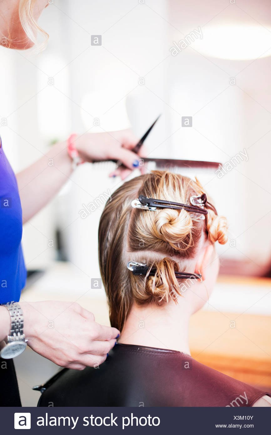 Woman with hair clips in hair in salon - Stock Image