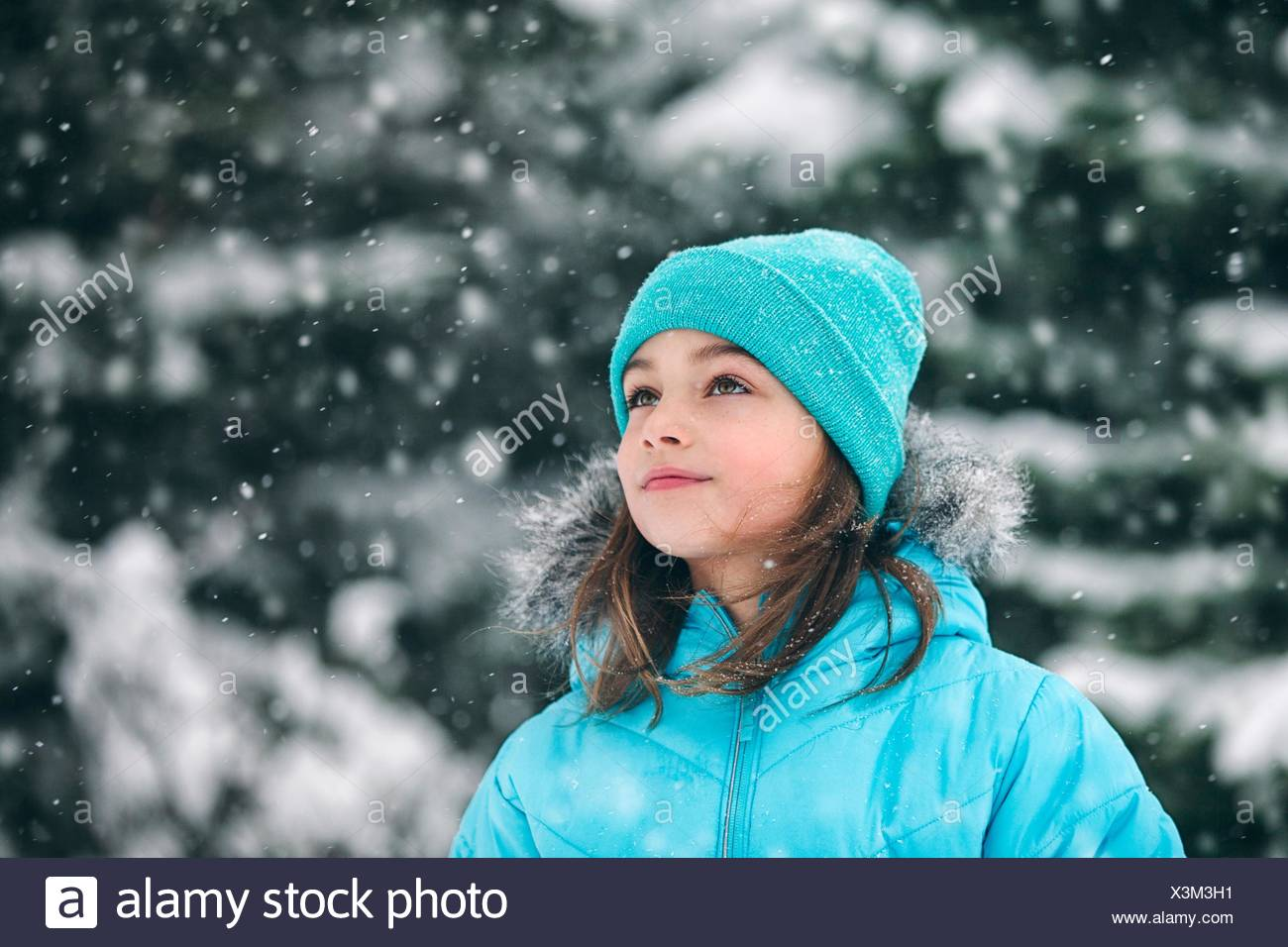 Girl wearing knit hat looking away, snowing - Stock Image