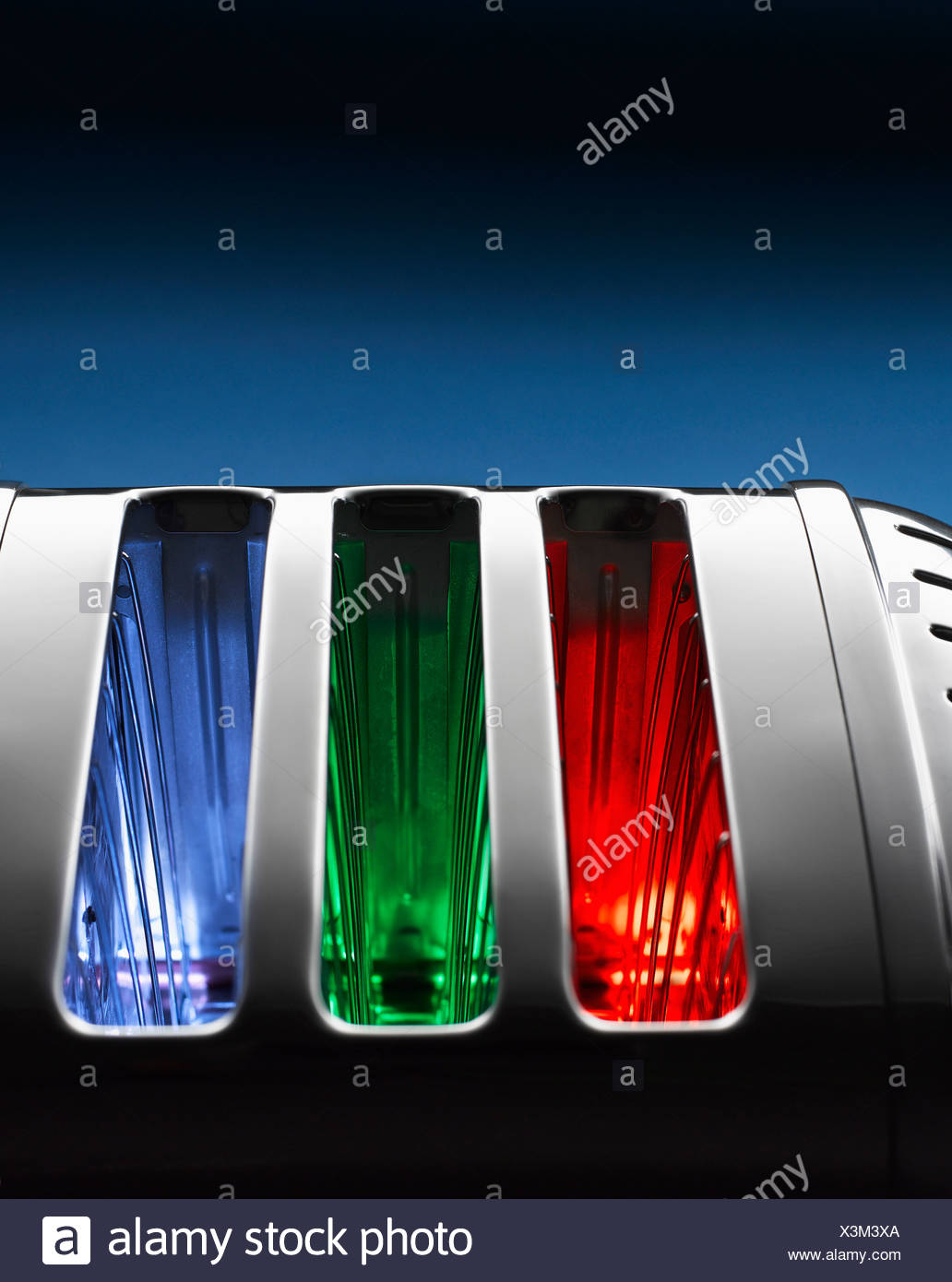 Multi coloured toaster against blue background - Stock Image