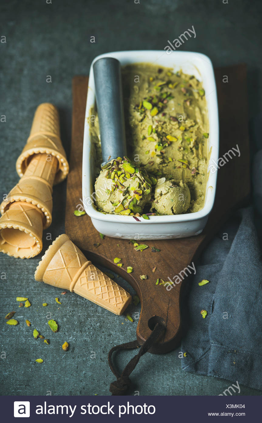 Homemade pistachio ice cream in ceramic mold with metal scooper, crashed pistachio nuts and waffle cones over dark concrete background, selective focu - Stock Image