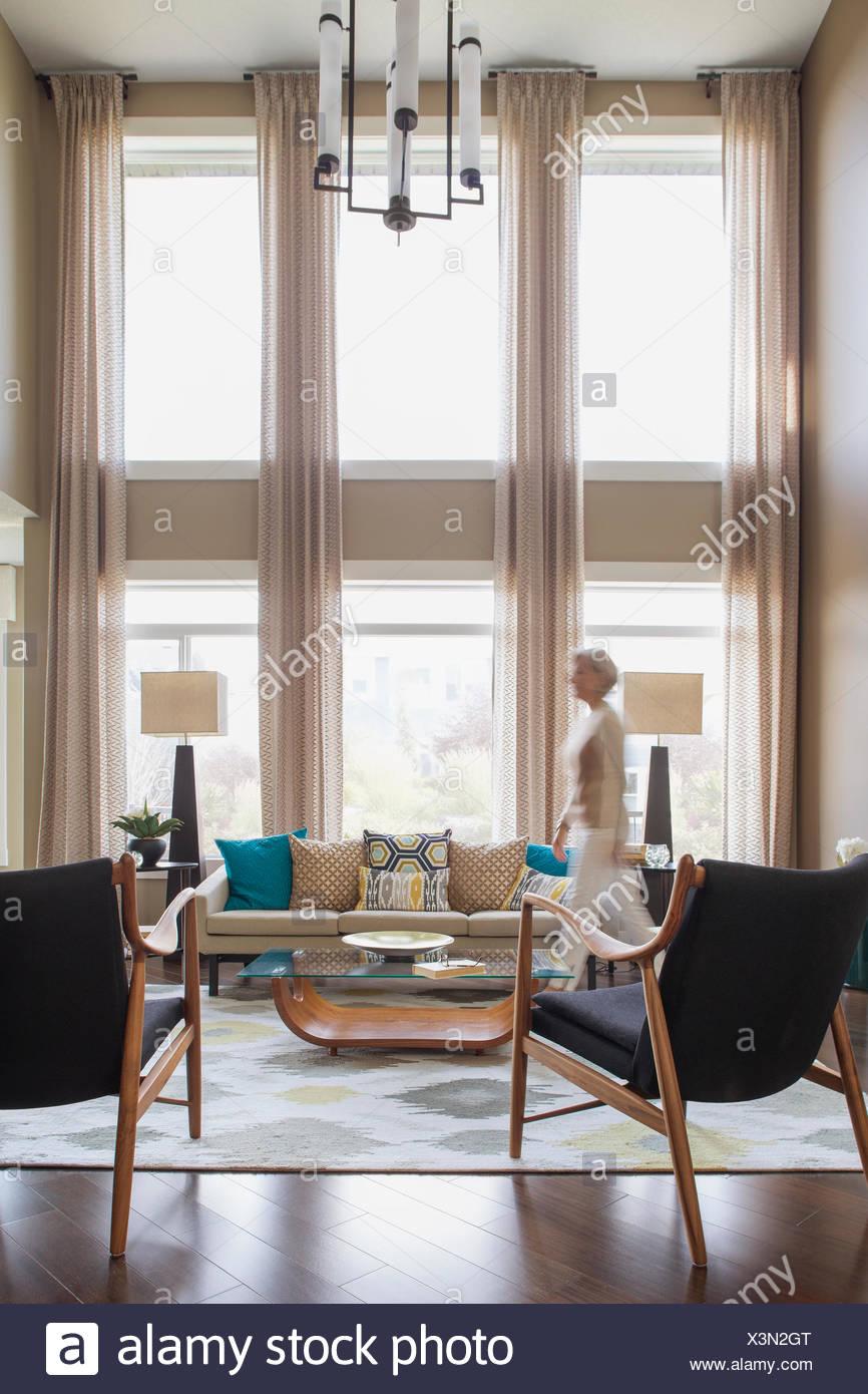 Woman walking in modern living room - Stock Image