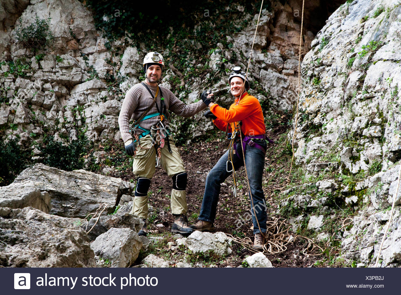 Italy, Two men wearing safety harnesses standing in front of cave - Stock Image