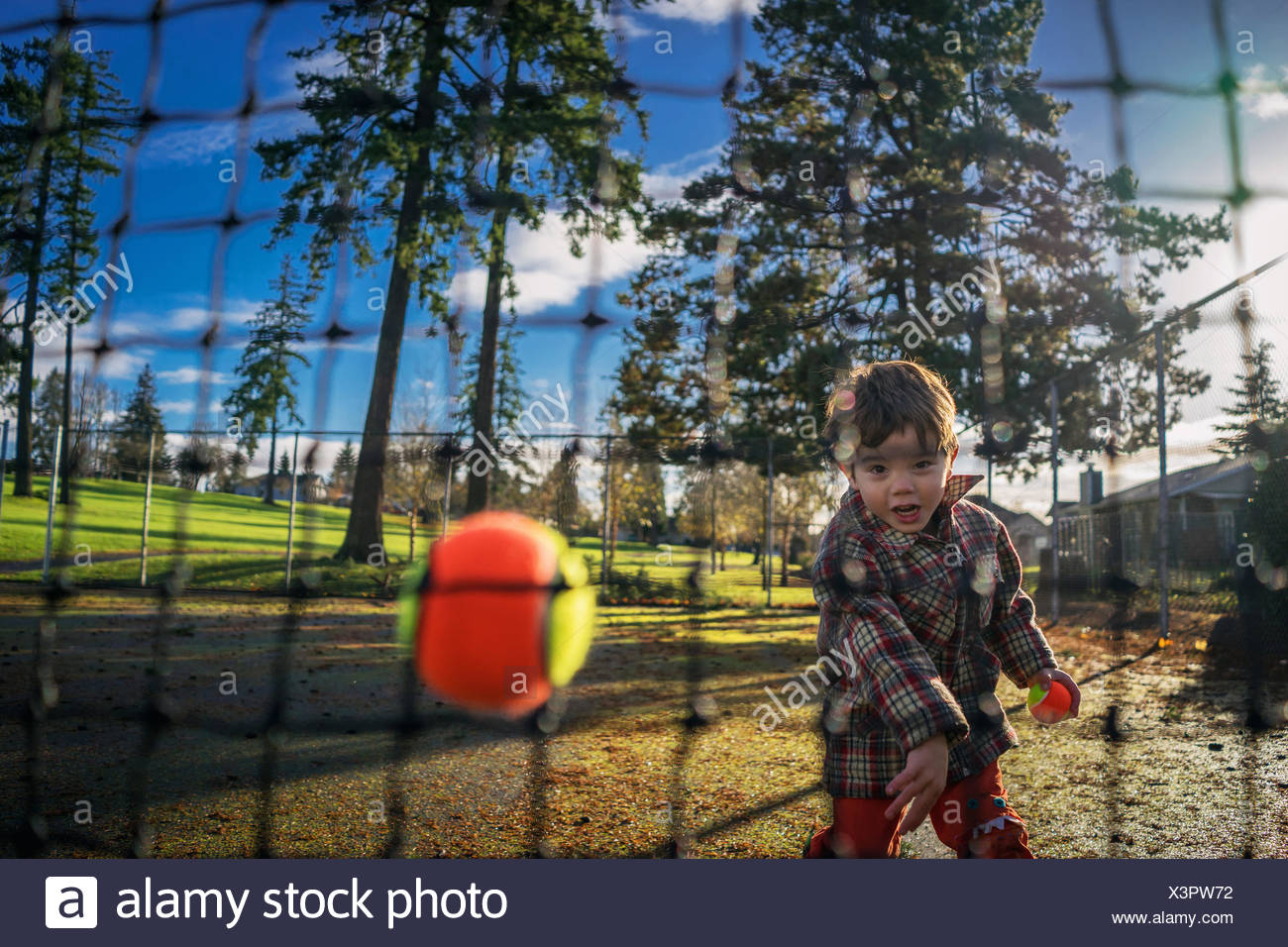 Young boy throwing tennis ball at a net - Stock Image