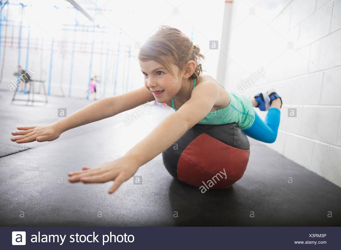 Girl balancing on medicine ball - Stock Image