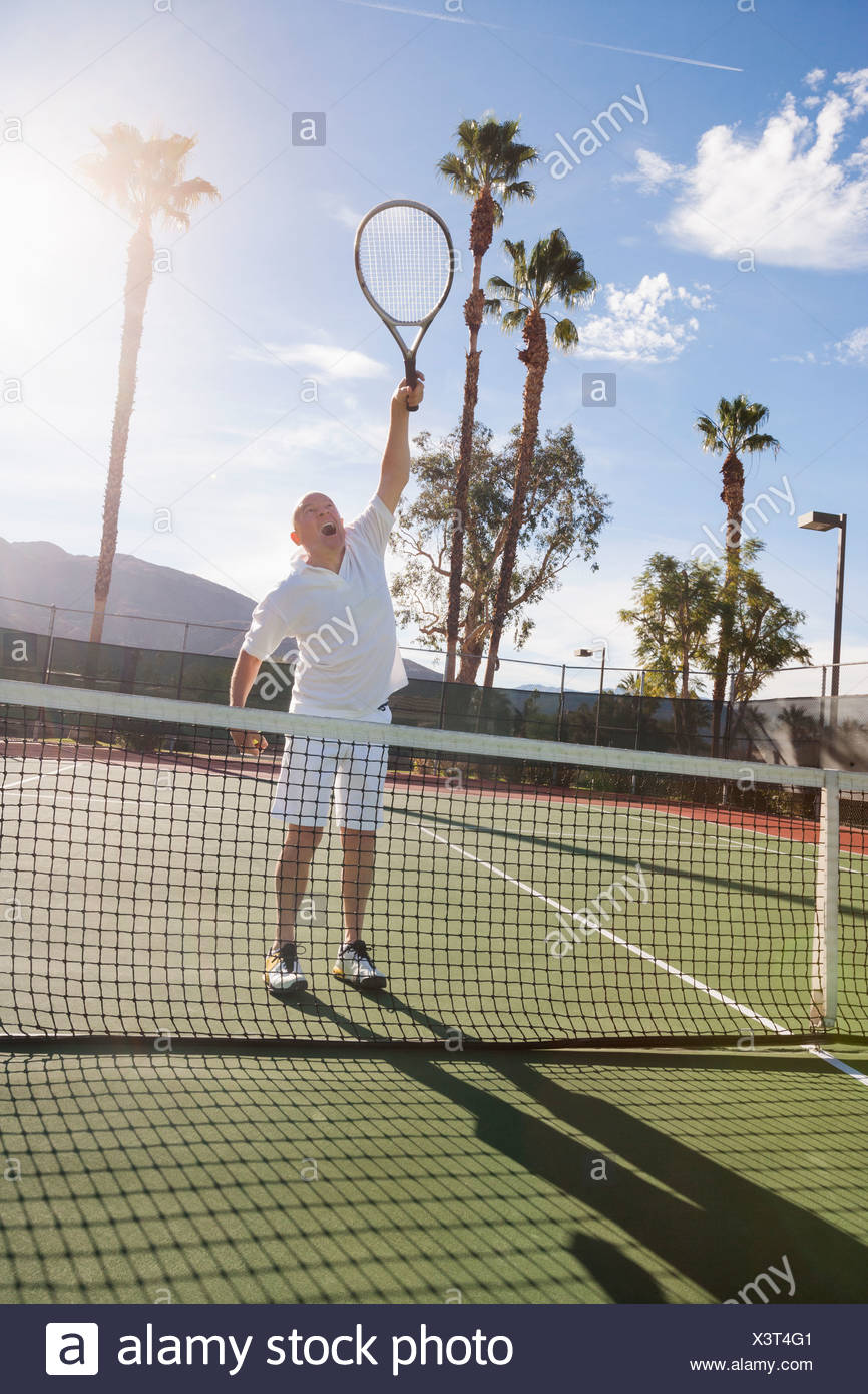Senior male tennis player playing on court - Stock Image