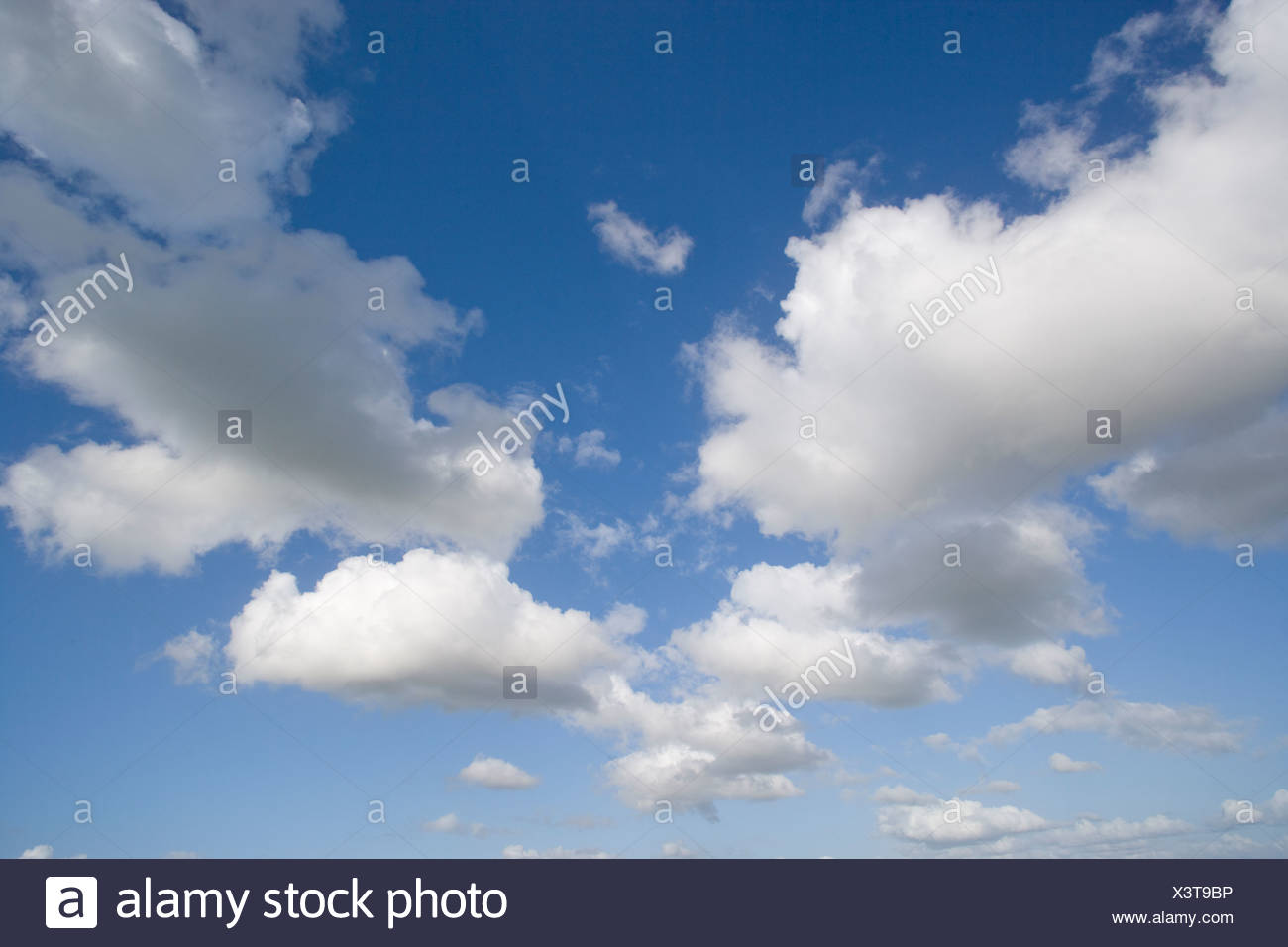 Clouds in sunny blue sky - Stock Image